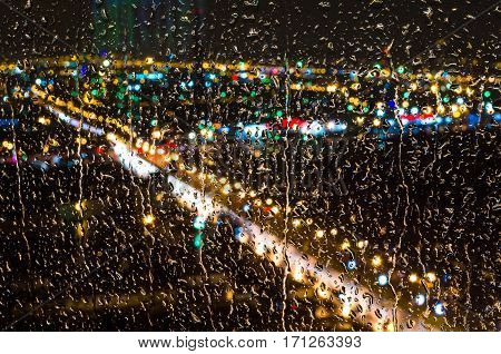 Raindrops on the glass and the lights of the city at night