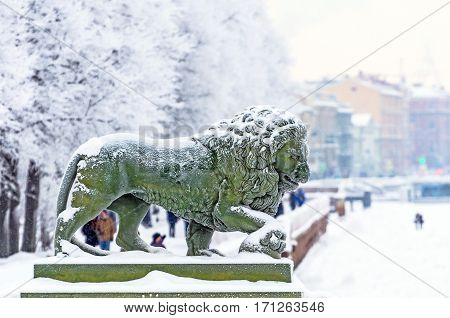 Winter embankment of the Neva River, snow lion statues