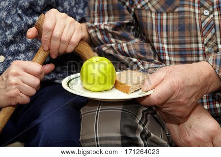 Old Couple. Poverty. Apple And Bread
