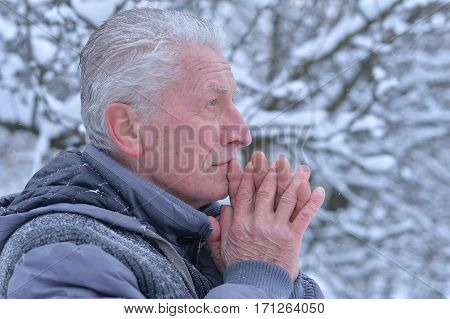 Old man praying to god with crossed hand in snowy winter