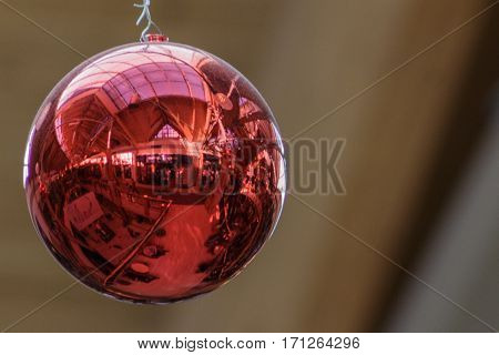 Red ornamental ball close up reflecting the mall at Christmastime.