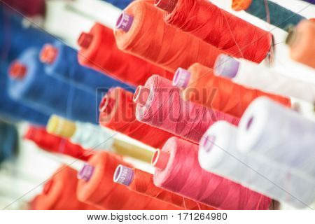 spool of woolen threads order colorful, red, white, blu