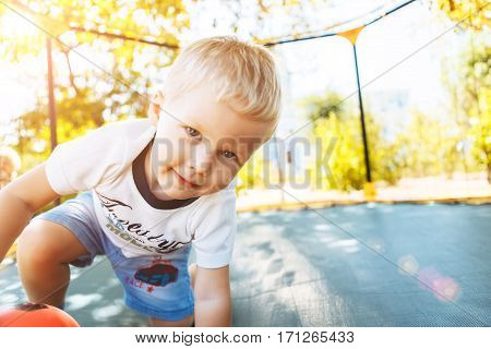 Boy playing jumping on a trampoline looking at the camera smiling having fun