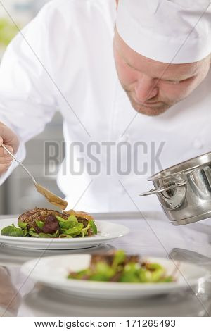Focused chef adds gravy to a meat dish in a professional kitchen at gourmet restaurant or hotel.