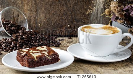 Cappuccino coffee and sweet chocolate brownies cake. A cup of latte, cappuccino or espresso coffee with milk put on a wood table with dark roasting coffee beans. Drawing the foam milk on top.