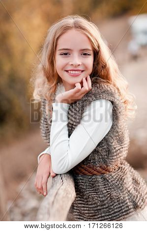 Smiling teen girl 12-14 year old wearing stylish fur vest and knitted sweater posing outdoors over nature background. Looking at camera.