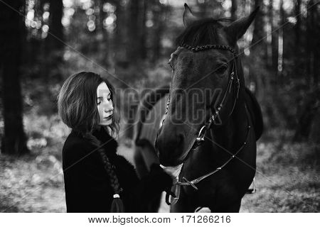 brave red-haired girl in a black coat with long hair gathered in a braid in the autumn forest a beautiful stallion strong woman standing next to a horse horse portrait mammal