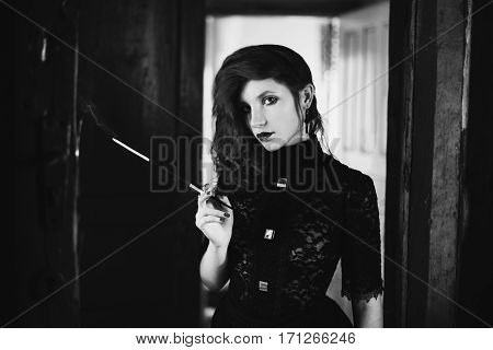 red-haired girl with red lips in a dark room a woman holds the mouthpiece with a cigarette in his hand pale skin a door in the background retro style noir black dress