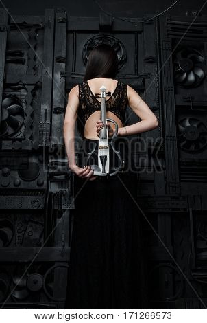 A slender woman in a black dress standing with a violin sideways to the photographer. On the background of the black metal door. Vertical photo