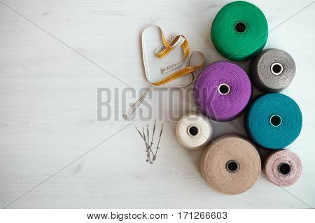 coil of woolen threads background gray wood