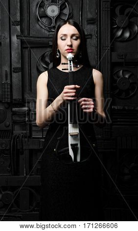 Portrait of a young woman with a violin. In a black dress. Hands holding a violin. Closed eyes