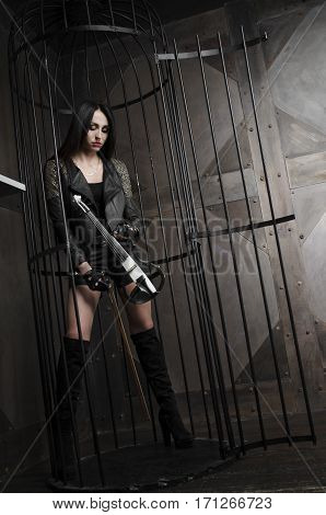 Beautiful girl holding a violinstanding in a cage. In long boots and a leather jacket short shorts.