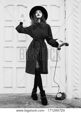 red-haired girl with red lips and pale skin with a black hat and red coat in an elegant stylish woman in black boots in tights with a red rotary phone the phone receiver in hand on white background