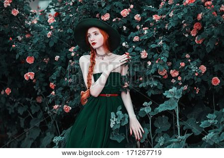 Red-haired girl with blue eyes and pale skin in a green hat and dress with a red belt. Woman with long red plait against the backdrop of bush peach roses. Red lips a necklace around his neck. Bright unusual appearance.