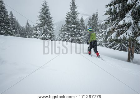 Man traveler goes in snowshoes through the alpine meadow during snowfall - winter adventure in the mountains.