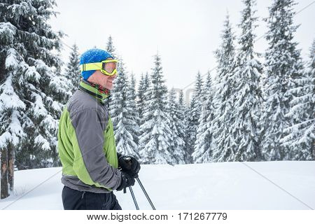 Traveler man in goggles is relaxing on the alpine meadow during snowfall and looking into the distance - winter adventure in the mountains.