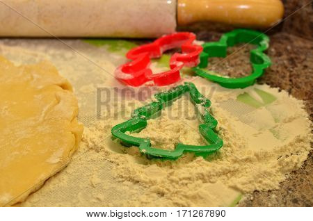 Christmas baking preparations and cookie cutters in flour