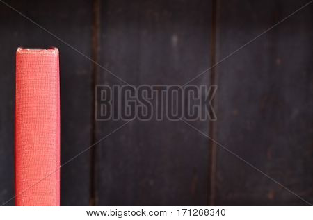 Red antique book spine on old wooden bookshelf background