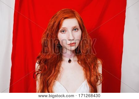 The blue-eyed redhead girl with a pendant around the neck on a red background. Natural beauty. Bright unusual appearance.