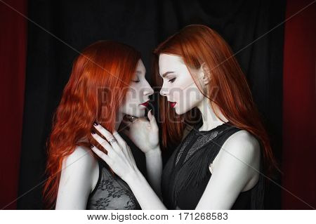 Two girls in red pale translucent sexy underwear hugging each other on a black and red background. Gloomy young beauty reminiscent of porcelain dolls. Gothic subculture. Gentle lesbian