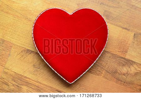 Velvet heart shaped box on a wooden background