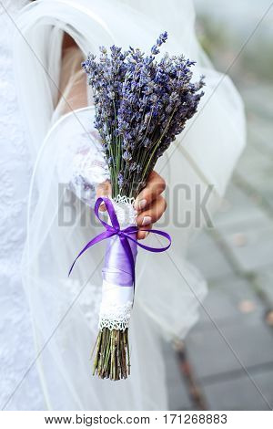 Wedding bouquet of lavender in the hands of women. The concept of marriage and love.