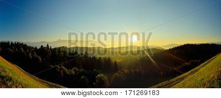 Summer High Tatras mountain landscape. Sunrise at monumental hills. Golden colored forest and peaks. Fog and inversion