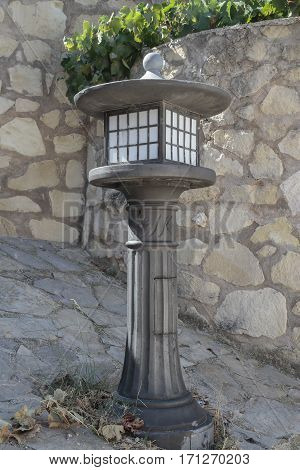 vertical view of an iron lamppost on a nice stone corner of the street