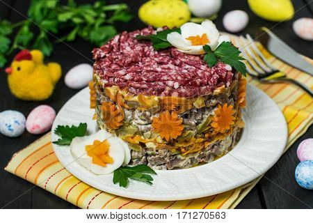 Multilayer festive salad with beef pickled cucumbers and carrots on a blue wooden table with eggs and chicken. Easter food Easter recipe. Selective focus