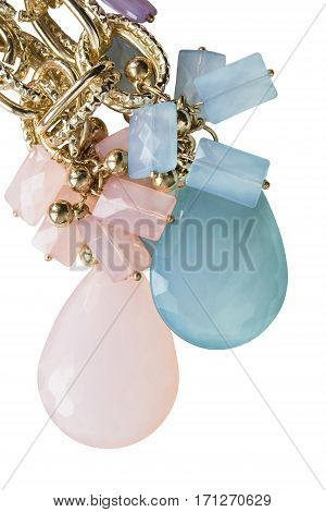 Colorful crystal trinkets and gold closeup on white background