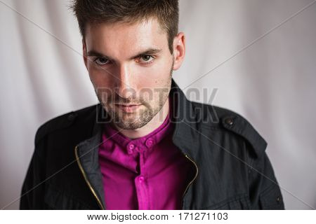 stylish portrait of a young man in a purple shirt and a black jacket on white background ooking at the camera
