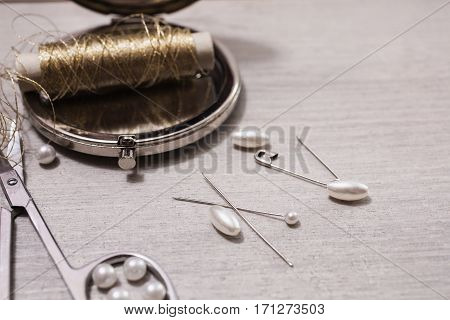 Reel gold thread on a wooden background. Needles and pearls for needlework. Tools for sewing. Fasteners for bra. The process of creativity. seamstress table. Findings .Retro