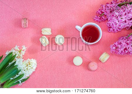 Beautiful spring holiday background. Cup of tea fresh white and pink hyacinth and sweet berry and vanilla macaroons cookies on pink copy space groundwork.