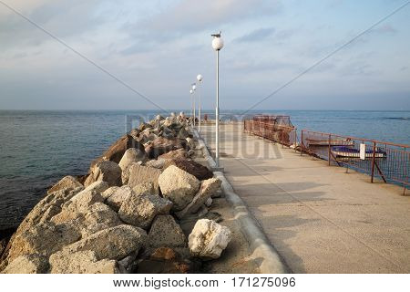 Breakwater extending in the sea. Pierce with lampposts. Calm summer day on the coast of the Black Sea.