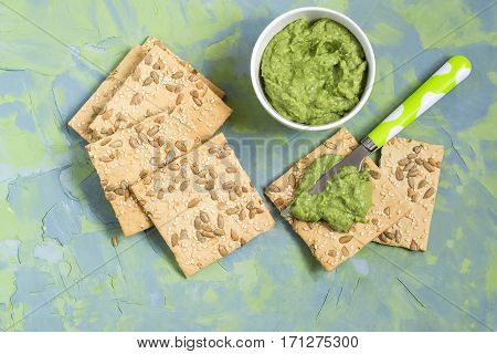 Homemade wholegrain crackers with sesame sunflower seeds and guacamole on blue-green textured background. The concept of diet and healthy eating. Top view