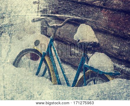 Old bicycle in the snow in the countryside. Photos in a grunge style.