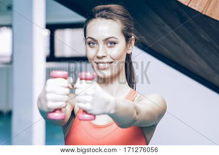 Smiling Woman Lifting Weights In The Gym