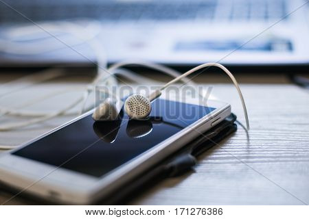 Headphones and smartphone on the table to listen to music.