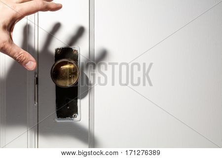 old wooden door with door knob hand shadow.