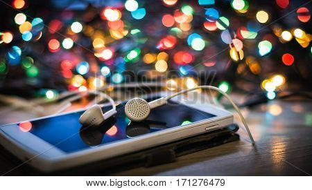 Headphones and smartphone on the table to listen to holiday music.