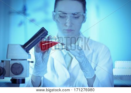 Scientist pouring sample into a Petri dish in laboratory