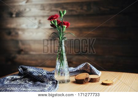 delicate bouquet of carnations in a vase on wooden table.