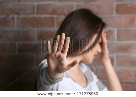 Depressed young woman with outstretched arm on brick wall background