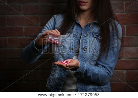 Young woman using pills for commit suicide on brick wall background