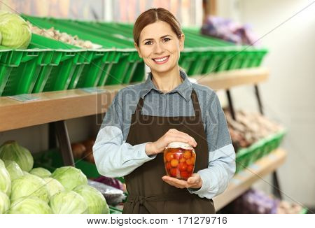 Beautiful saleswoman holding jar of pickled tomatoes in market