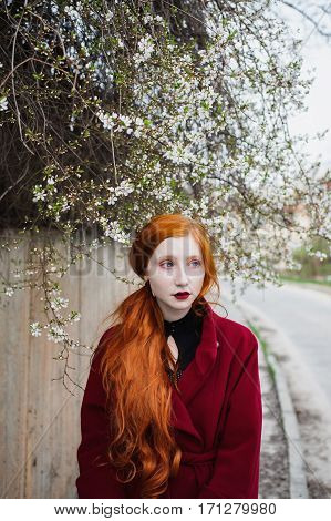 Pretty red-haired girl in a burgundy coat on the stairs. Spring Glamour portrait in retro style. Styling by fifties. Woman with long orange hair.