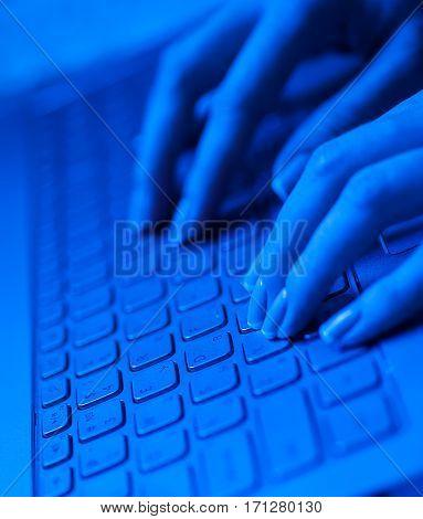 Woman fingers on the laptop keyboard in blue tones.