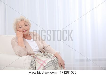 Elderly woman propping up face sitting in armchair at light room