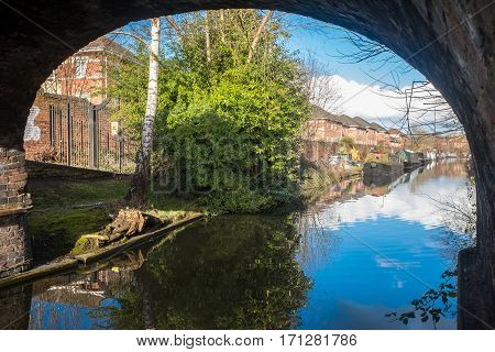 VIew of Birmingham Canal on a Sunny day showing some canal boats, houses, trees and blue sky.