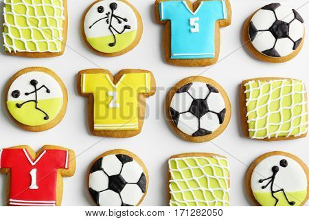 Delicious gingerbread cookies decorated with football signs on white background